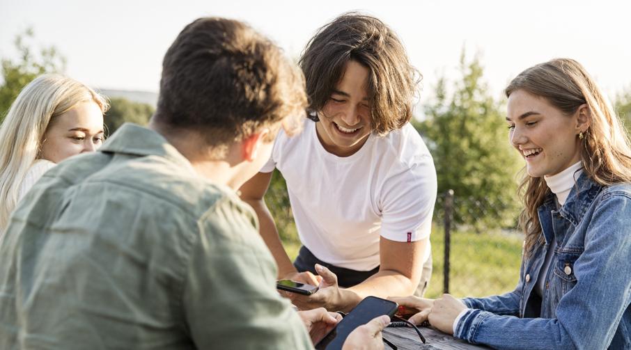Fire ungdommer med telefoner rundt et bord ute.